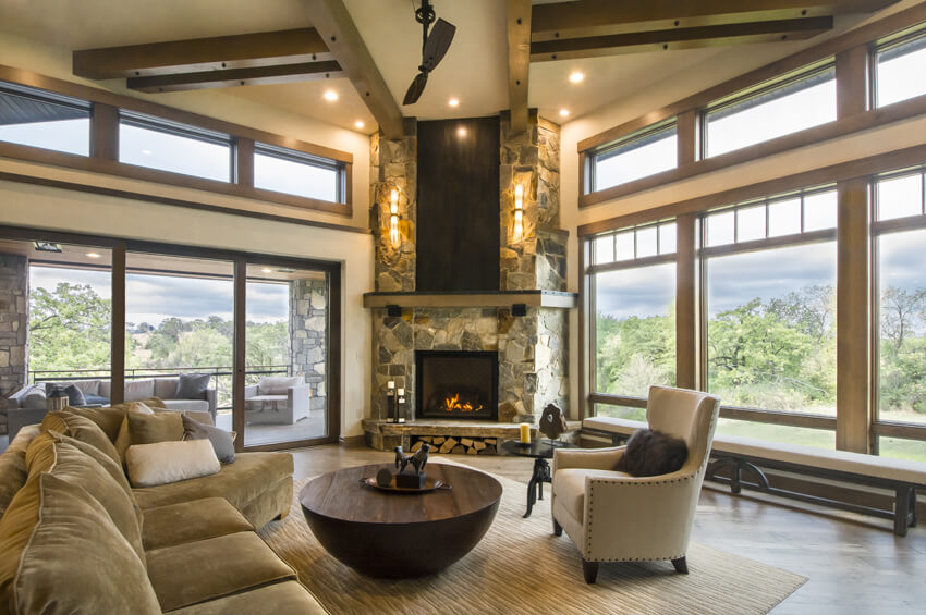 great room with timber beams and large windows