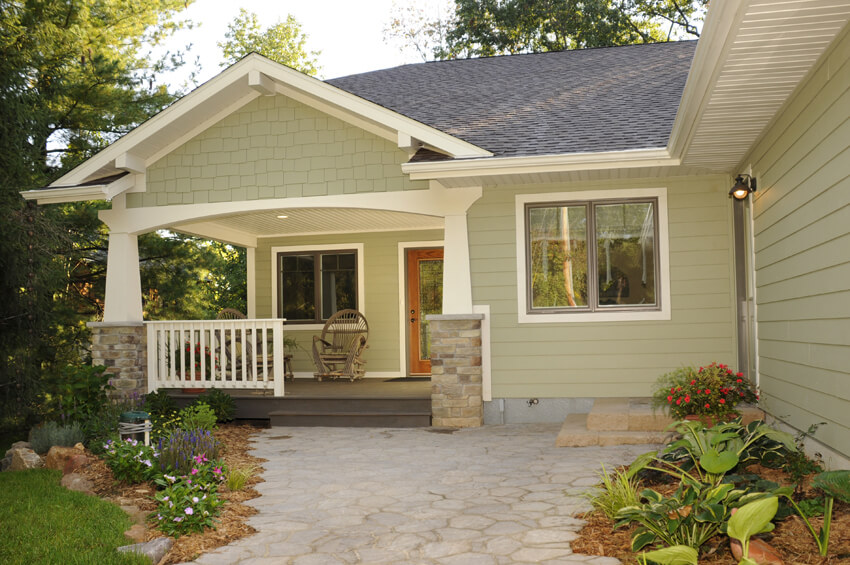 green ranch home with covered front porch