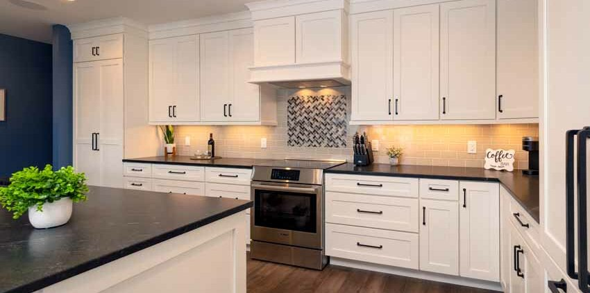kitchen with white cabinetry and black countertops